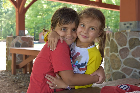 two young kids hugging and smiling at camera