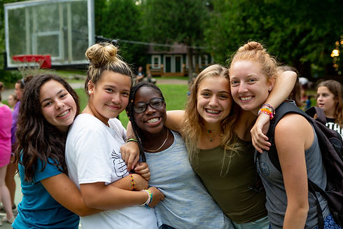 group of 5 female teen campers smiling and hugging