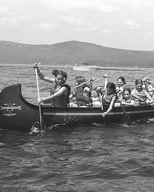 Black and white image from the 1990s of girl campers paddling a canoe