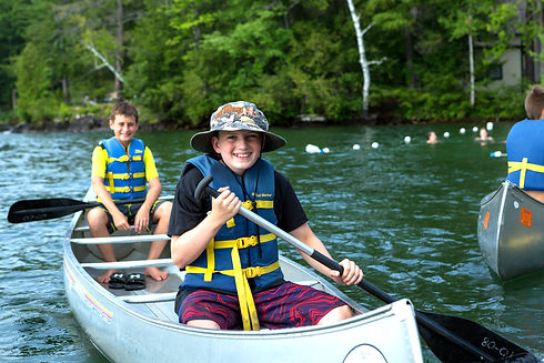 two boys in lifejackets canoeing on lake george