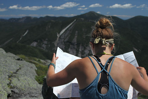 girl reading a hiking map on a mountain summit