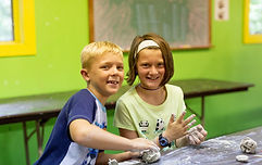 a boy and girl camper molding clay in arts class