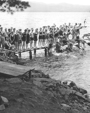 Black and white image from 1927 of boys jumping off dock into lake