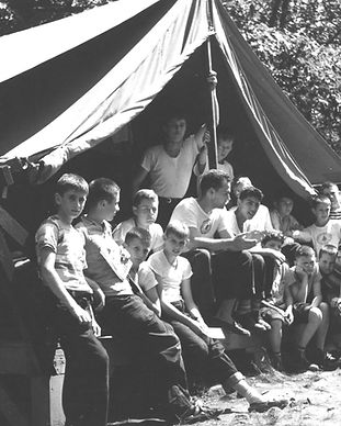 Black and white photo of campers in front of a large tent in the 1950s