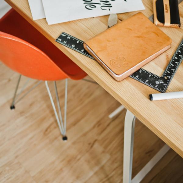 Mesa de um escritório com caderno, lápis e régua
