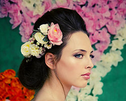 אישה בתסרוקת מנופחת ומלכותית עם סיכות פרחים