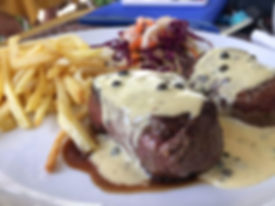 Beef filet toppd with Madagascar green pepper sauce served with a crunch salad and French fries