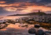 Northumberland coast seascape, Dunstanburgh, England, UK, featuring Dunstanburgh Castle at sunrise.