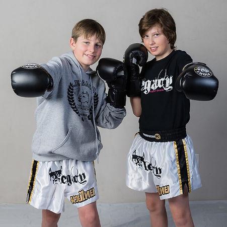Two kids wearing boxing gloves smiling