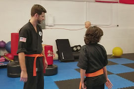 father and son work together on a martial arts rehearsed fight.  This is good practice as it develops the sense of timing and develops habit that increases reaction time & hand/eye coordination.