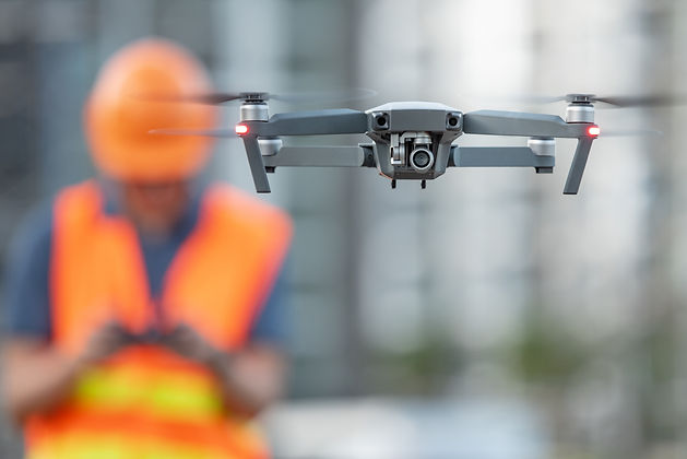 Young Asian engineer flying drone over c