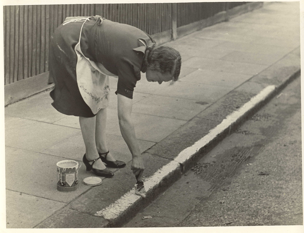 WW2 Woman painting curb, help during bla