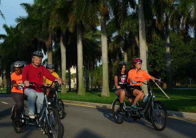 Bicyclists riding tandem and single bikes.