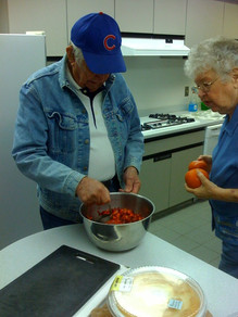 Cooking class: Two older adults prepare fruits and vegetables
