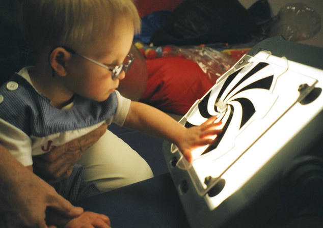 Young child reaching for a lightbox with a white and black spiral pattern.