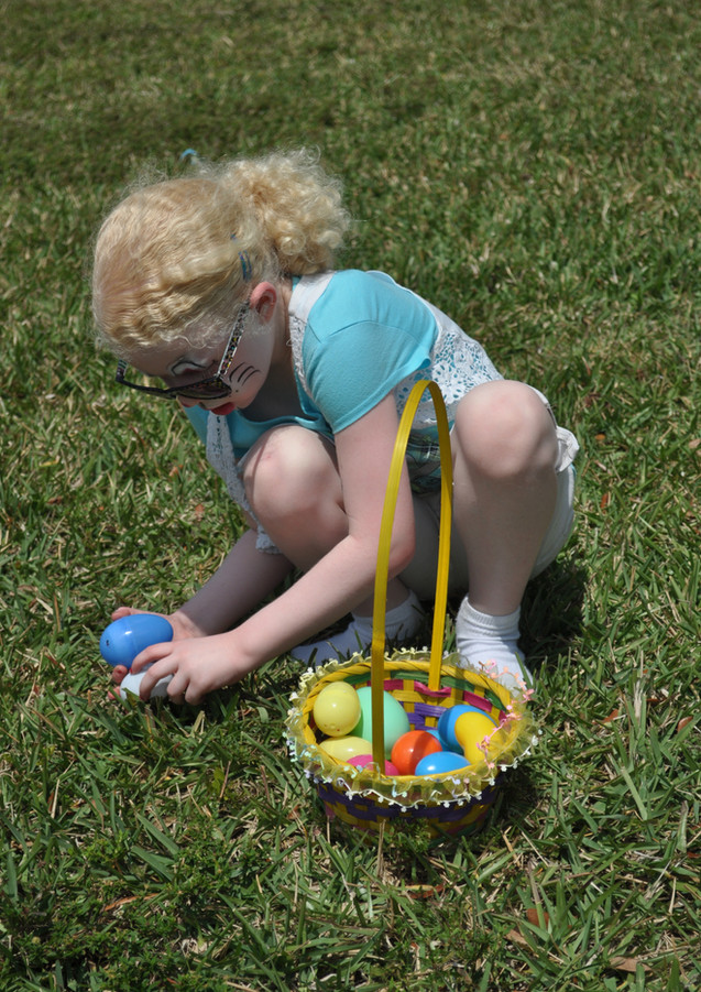 Easter Egg Hunt: Young Girl finding Easter Eggs