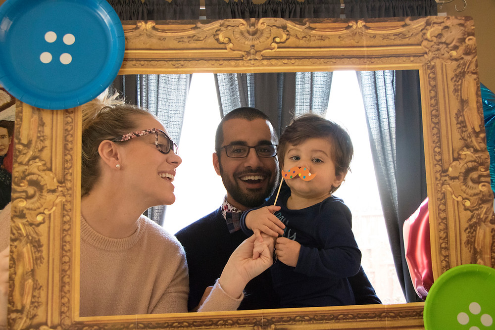 Dad is holding his son, Bishop while mom holds a fake moustache on his face. All three are inside a frame with big buttons on the corners