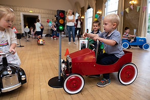 Boys and girls having fun in vintag pedal cars.