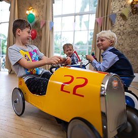 Children interacting at fun Dinky Drivers party,ridig in vintage pedal cars.