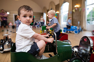 Boy riding vintage pedal car at Dinky Drivers party.