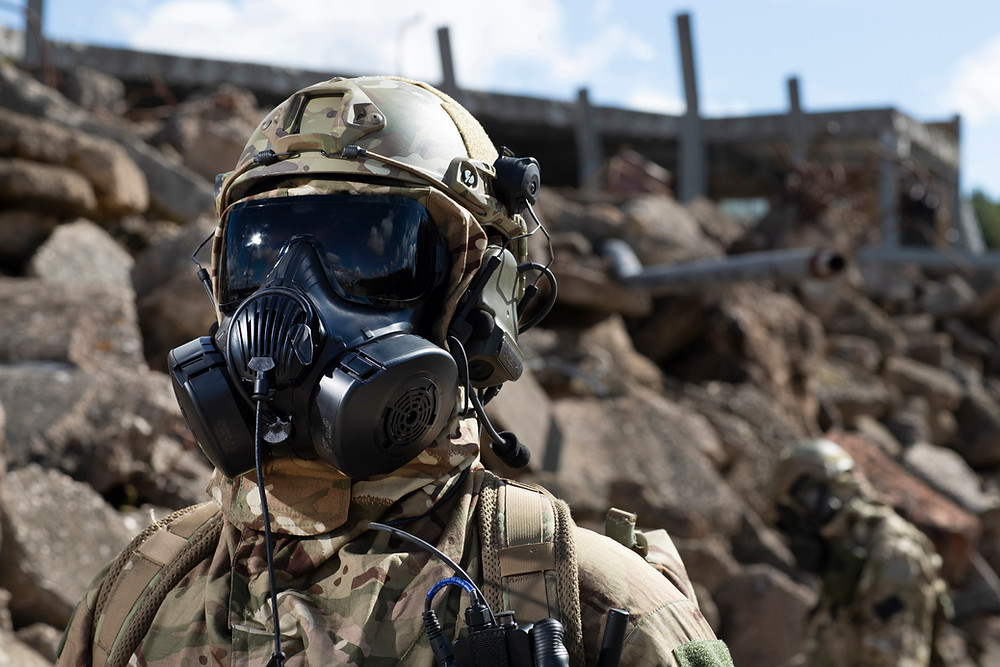 Soldier in foreground in front of an army barracks wearing Avon Rubber's M50 Mask System