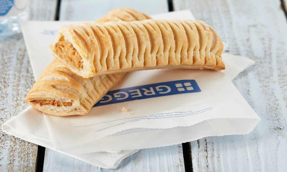 Two Greggs' sausage rolls balanced on Greggs' paper bags.
