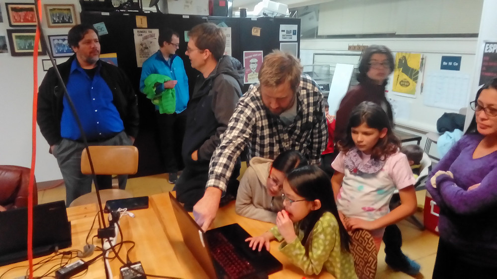 James helps two young girls as they learn to code their own video game, in preparation for the Global Kids Game Jam organized by Los Alamos Makers.