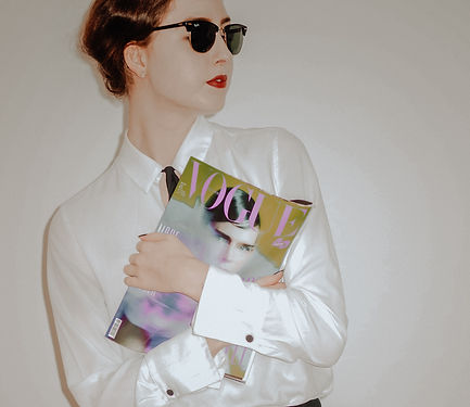 woman%20in%20white%20blazer%20holding%20white%20and%20blue%20plastic%20pack_edited.jpg