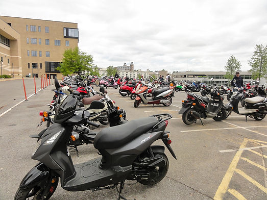 parking lot containing mopeds and micromobility devices