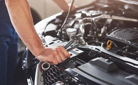muscular-car-service-worker-repairing-ve