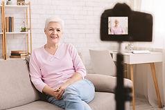 Cheerful senior woman blogger recording