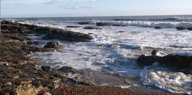 The seashore at low tide. The coast is tidal, and at low tide the water's edge is much further out than at high tide.