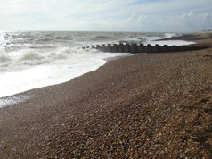 The wooden separations are called 'groynes'. They serve to hold the shingle (pebbles) so it builds up to a bigger beach area instead of getting washed away.