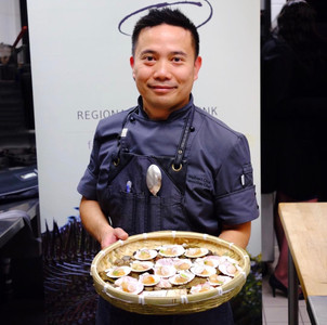 Chef Welbert Choi holding a platter of swimming scallops