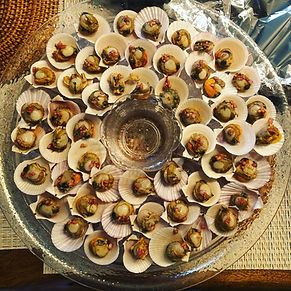 Party platter of chilled swimmig scallops served on the half shell with a mignonette sauce