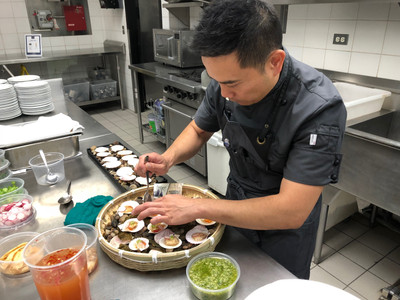 """Chef Welbert Choi preparing raw swimming scallops with Forage's 7-month old Herring """"Nuoc Man Cham', gingerand scallion confit"""