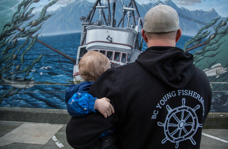 Joel Collier wearing a BCYFN sweater, holding Caleb Collier in front of a fishing mural