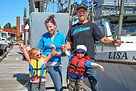 Joel, Melissa and thier two kids in front of their family fishing boat the Lisa Jess