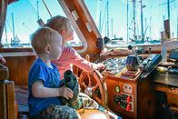 Joel and Melissa Collier's children at the helm of thier family fishing boat, the Lisa Jess