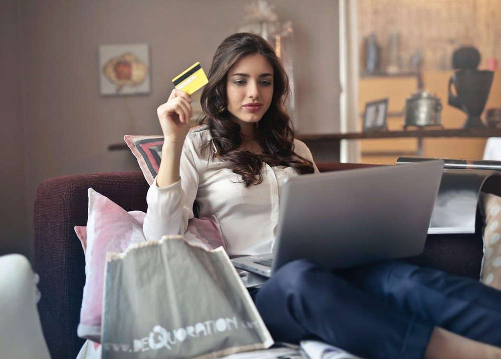 A woman holding her credit card shopping online through her laptop.