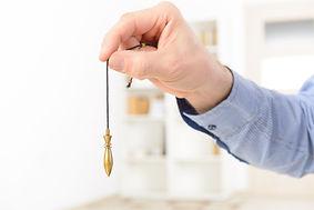 Hand Holding Pendulum