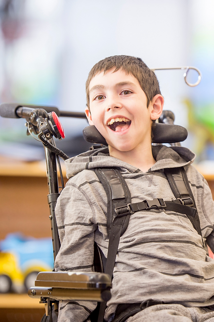 A young boy smiling, he is in a  wheelchair