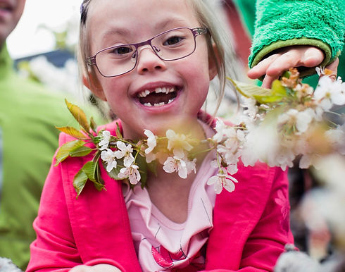 A young girl smiling with a floral lei around her neck