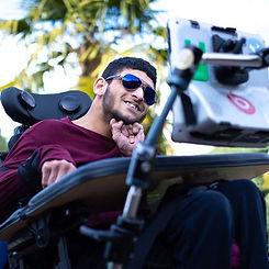 A man in a wheel chair wearing sunglasses and a  burgundy sweater, Karanveer Singh