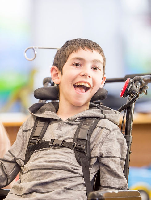 Young boy in a wheelchair smiling and using a headswitch