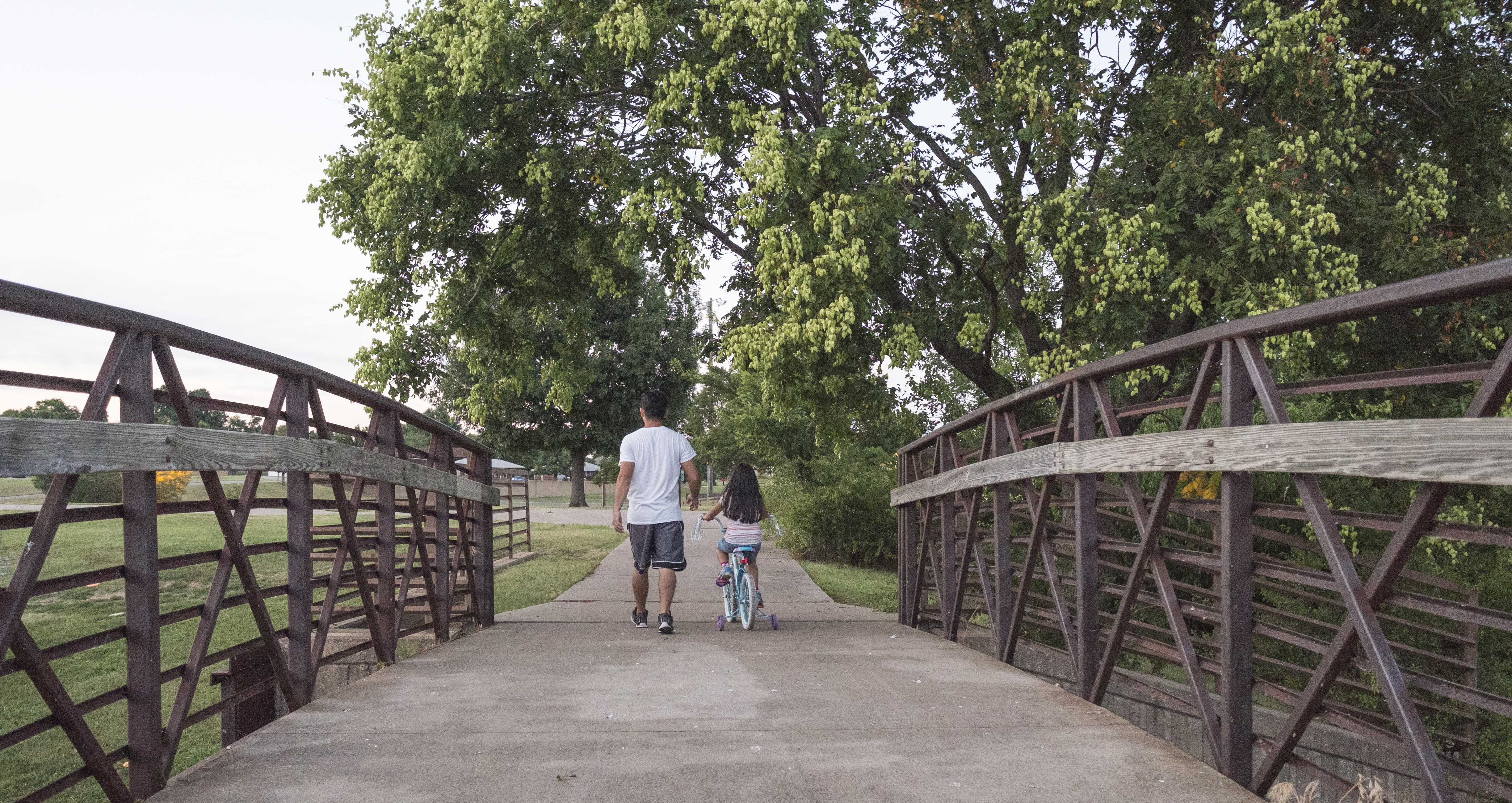 Father and daughter crossing bridge
