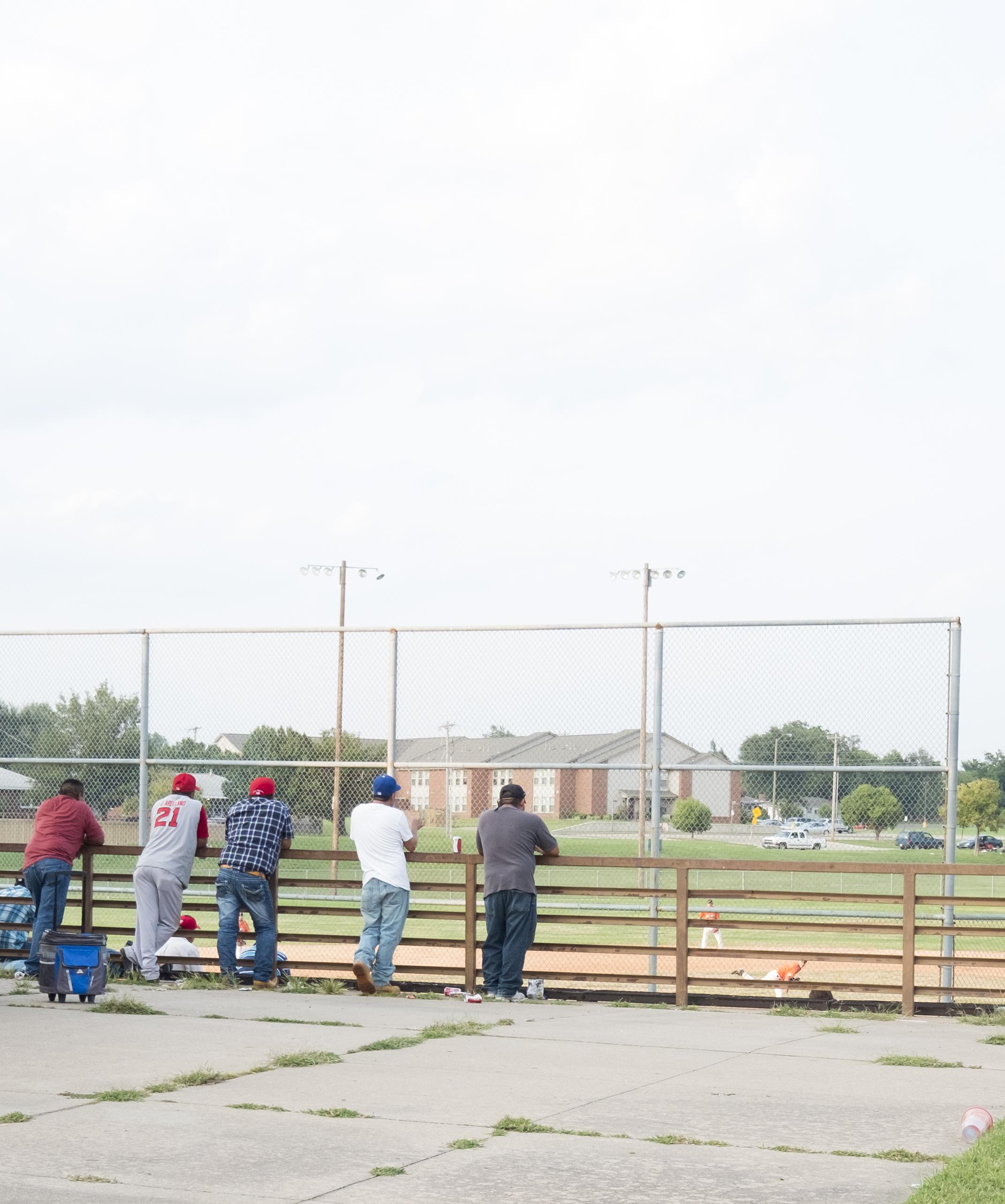 Dads watching kids play baseball