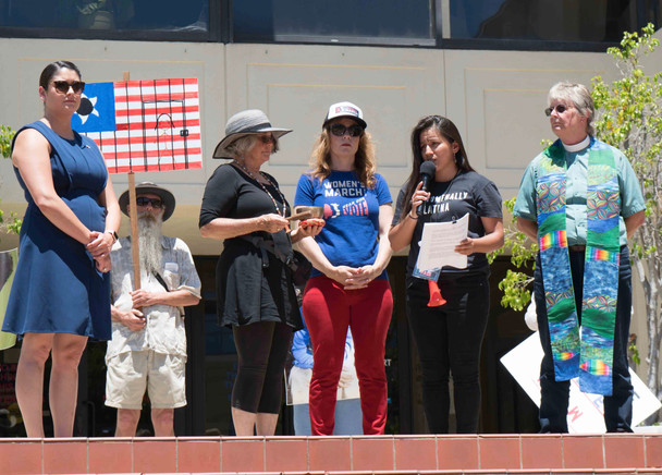 The Vigil: Sharon Rippner rings the bell as Rita Casaverde from Women's March SLO reads names of those who have died. Pastor Caroline Hall gave the invocation.
