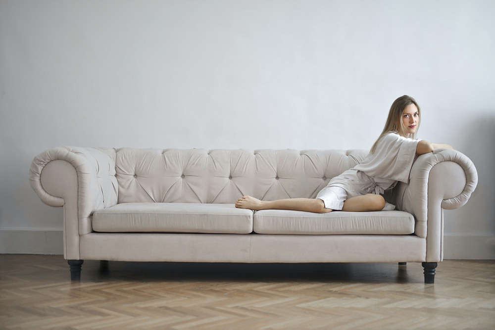girl on couch, couch in front of blank wall, girl in front of blank wall, white couch, white wall