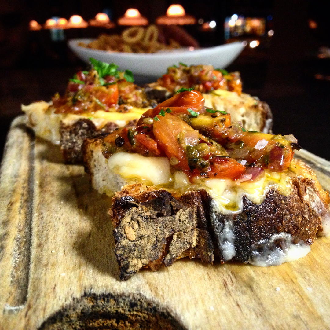 burnt tomato and broiled cheese crostini
